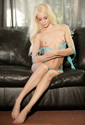 Blonde doll takes off tight dress and also then goes to underwear on the leather couch