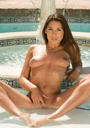 Good-looking model and xxx star Zafira poses in the pool on a hot sunny day